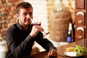 young wine taster smelling red wine