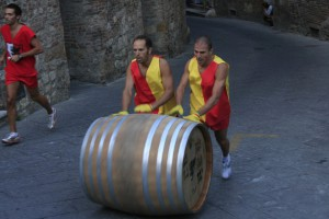two mean pushing a botte up the hill in Montepulciano