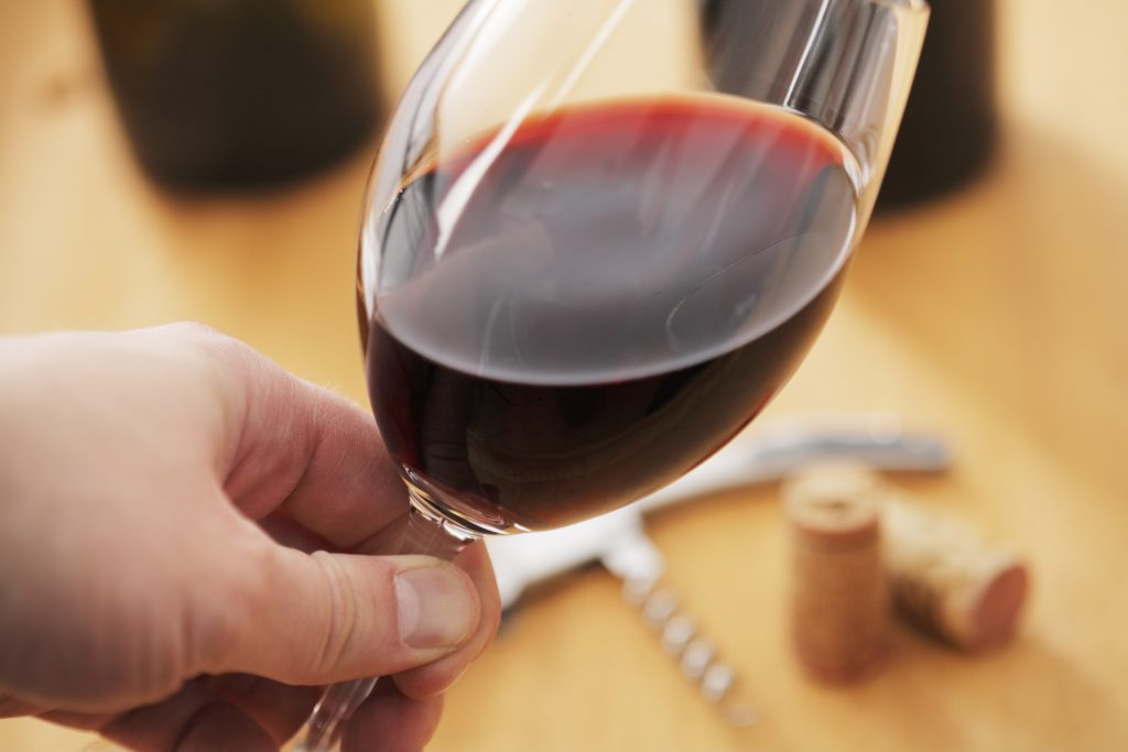 A Hand holding a glass of red wine while looking at the color of the wine